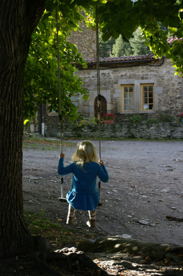 Cour intérieure du village avec petite fille qui fait de la balançoire devant l'église du 14e