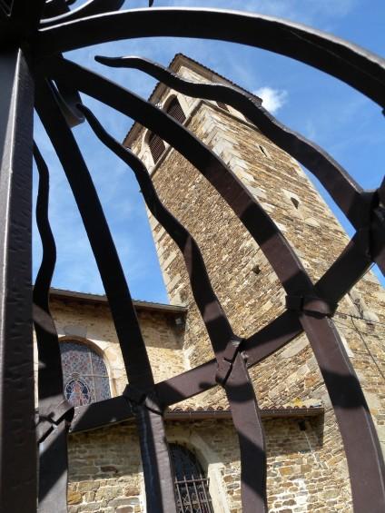 L'église médiévale de la Chartreuse de sainte croix en Jarez vue à travers la grille d'entrée (ferronerie d'art)