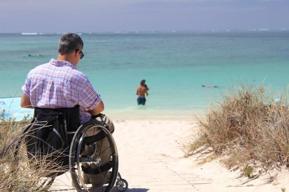 personne à mobilité réduite au bord de la plage face à la mer