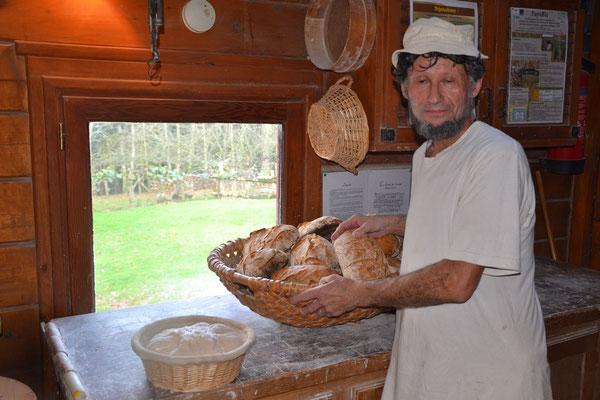 Un boulanger philosophe la main sur ses pains