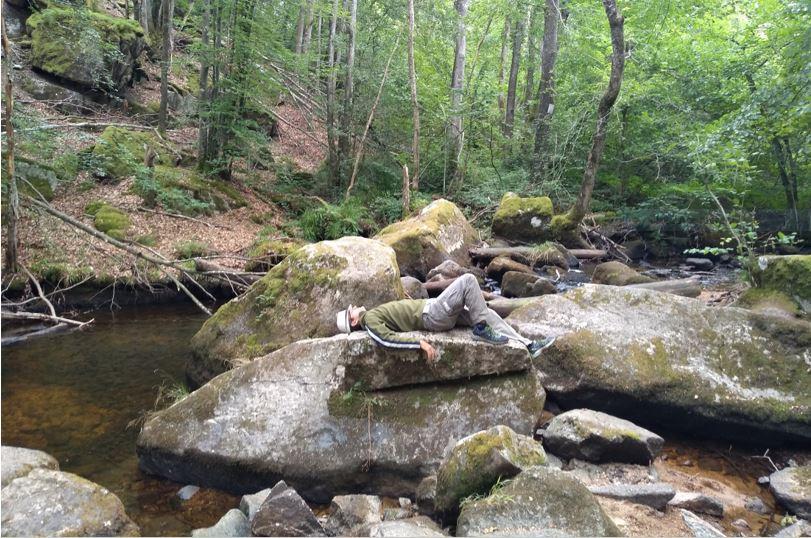 Retrouver la connexion avec la Nature. Manuel Miroglio allongé sur un rocher au milieu d'une rivière dans une forêt