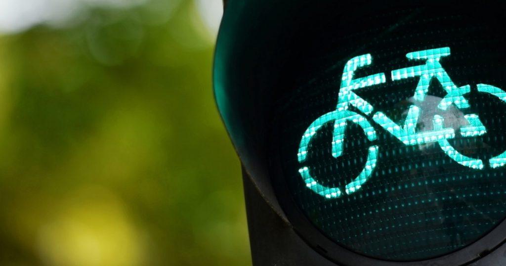un feu rouge montre un vélo qui passe au vert