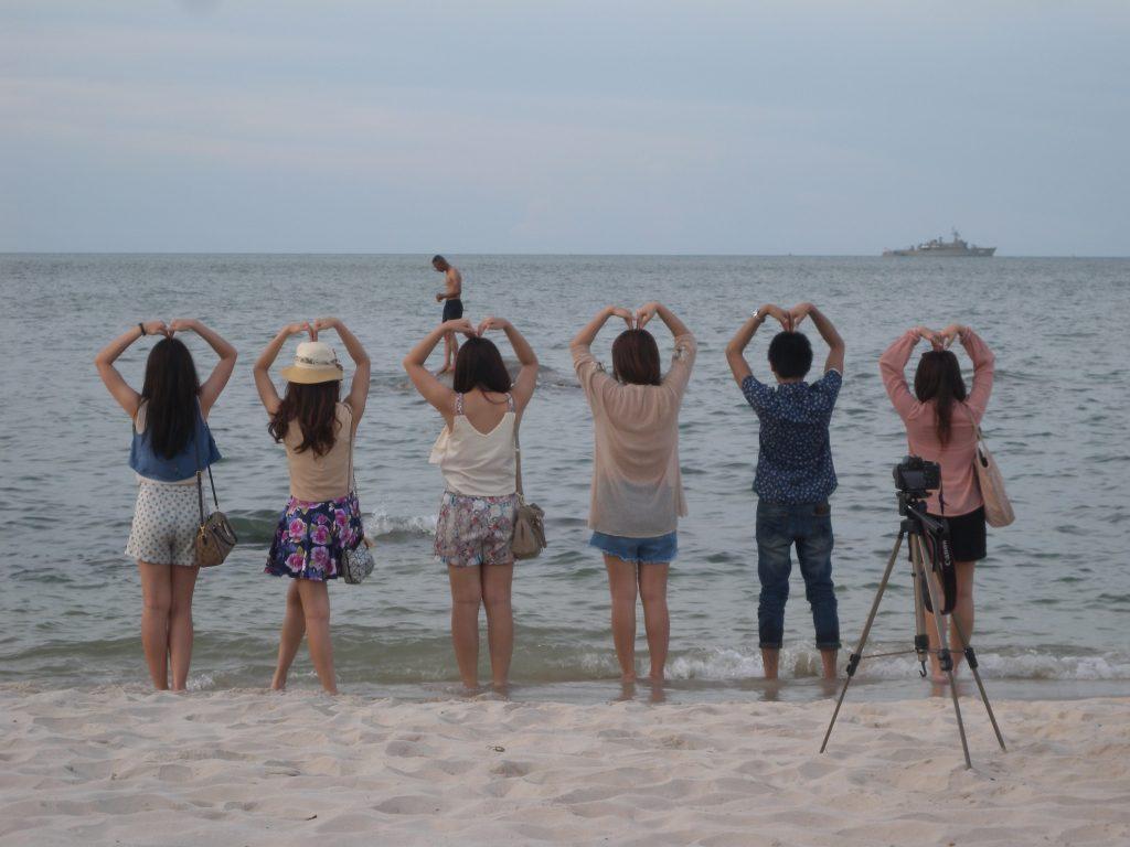 Jeunes filles thai sur une plage devant l'océan, les bras au dessus de leur tête formant un coeur