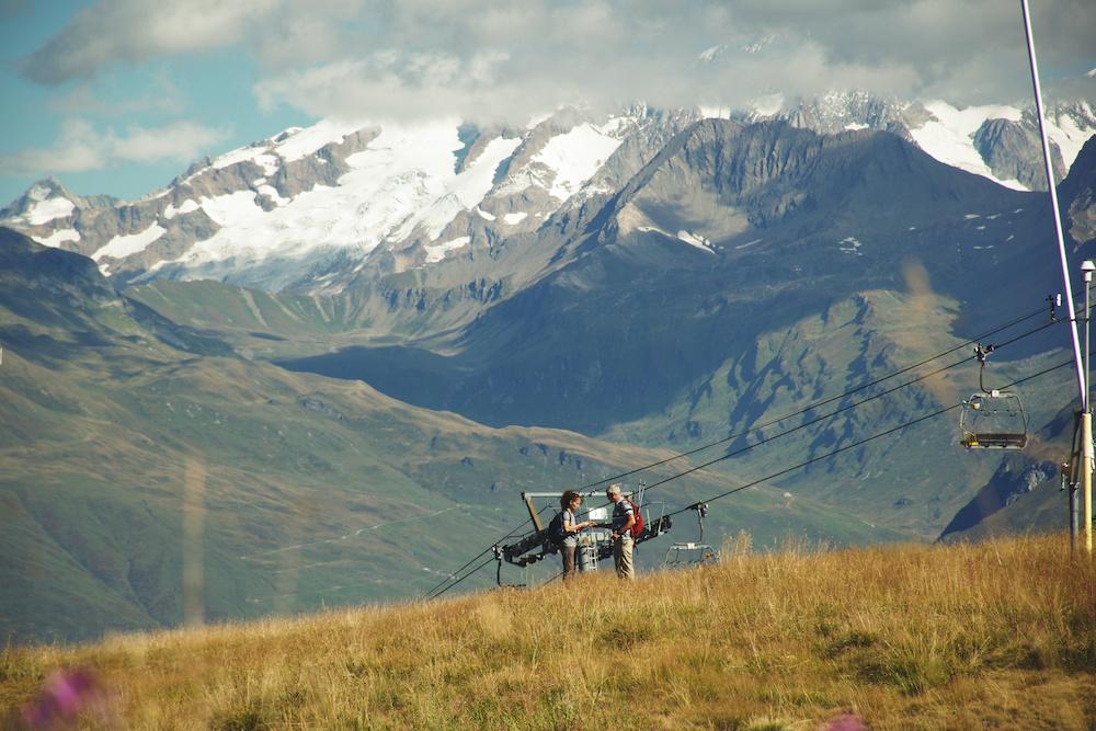 Paysage de montagne avec 2 personnes glânant des déchets et une chaîne de montagne en fond