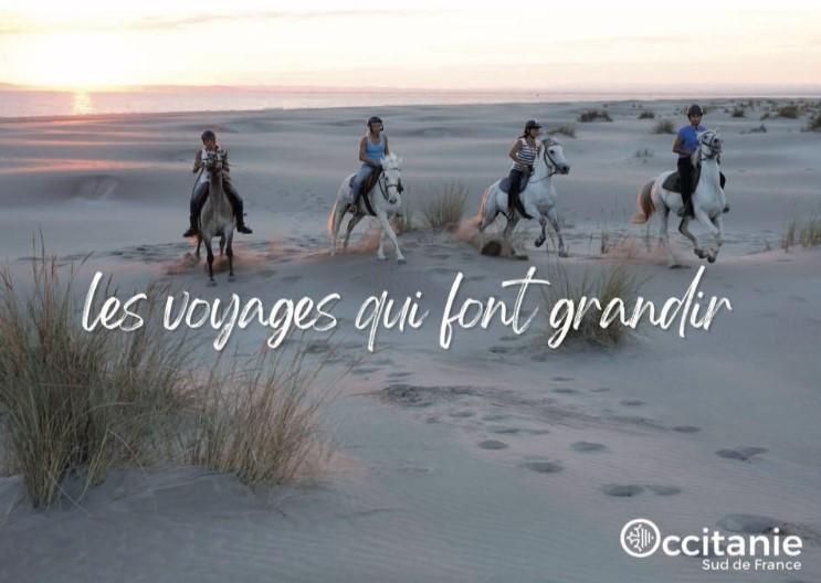 Des enfants sur des chevaux sur des plages d'Occitanie - avec le slogan « les voyages qui font grandir » écrit au centre