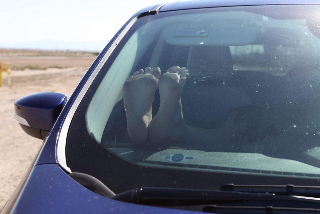 Sieste dans une voiture avec pieds nus collés au pare-brise. © Elisabeth Blanchet