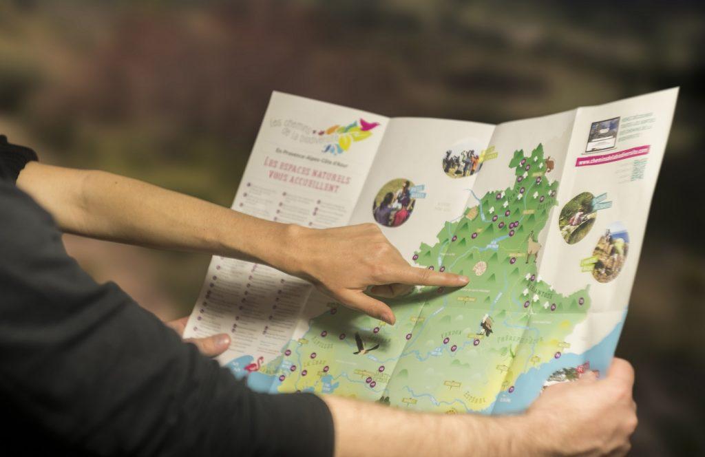 des vacanciers pointant une carte présentant les espaces naturels de la région Provence-Alpes-Côte d'Azur