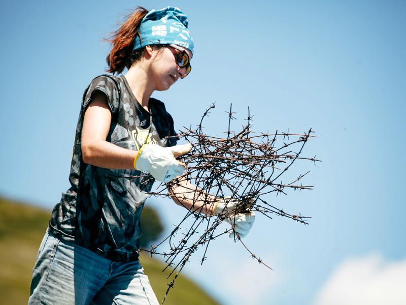 Fiona Mille présidente de Mountain Wilderness tenant à bout de bras des barbelés rouillés