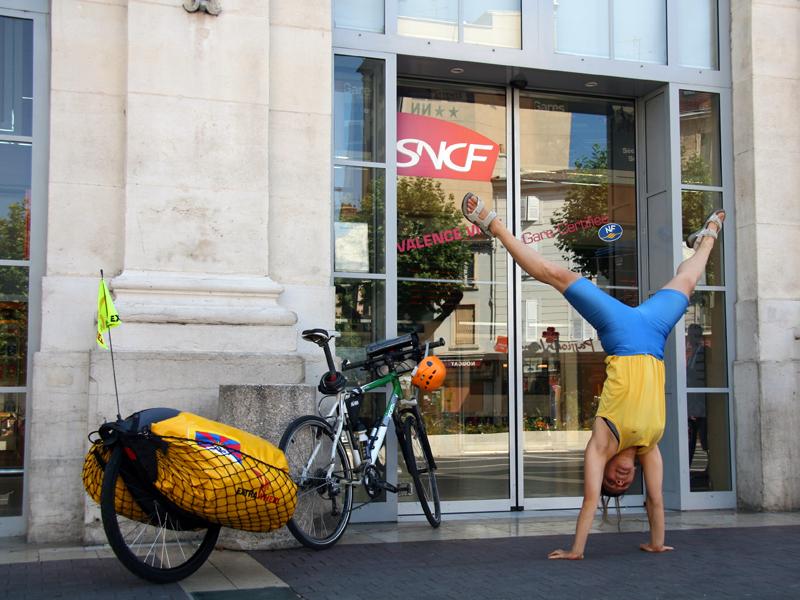 Fiona pose avec son vélo et sa remorque devant la gare de Valence lors d'une des campagnes 'Changer d'approche' mises en place par Mountain Wilderness.