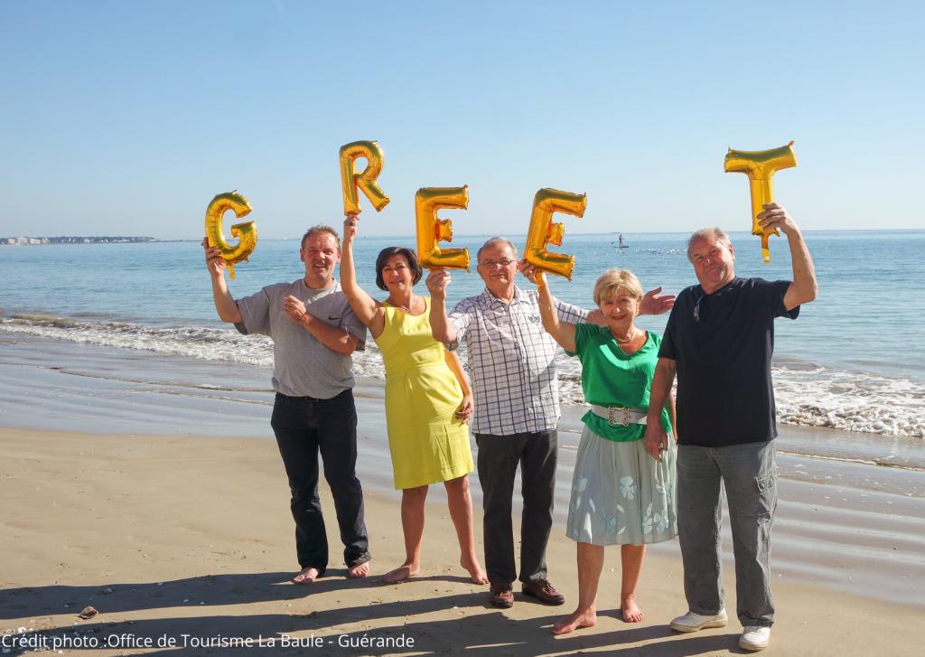 """Cinq Greeters posent avec les lettres du mot """"Greet"""" sur une plage de Guérande"""