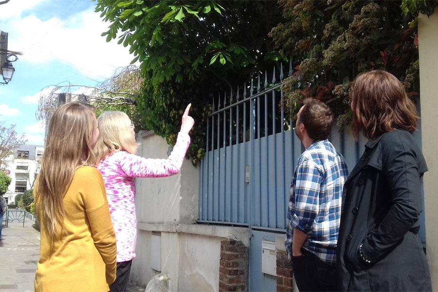 Un Greeter montre du doigt un arbre aux trois touristes