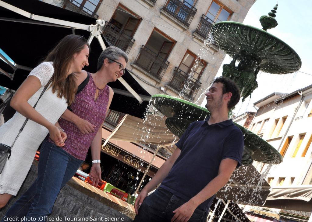 Un groupe en visite s'amuse devant une fontaine à Saint-Etienne