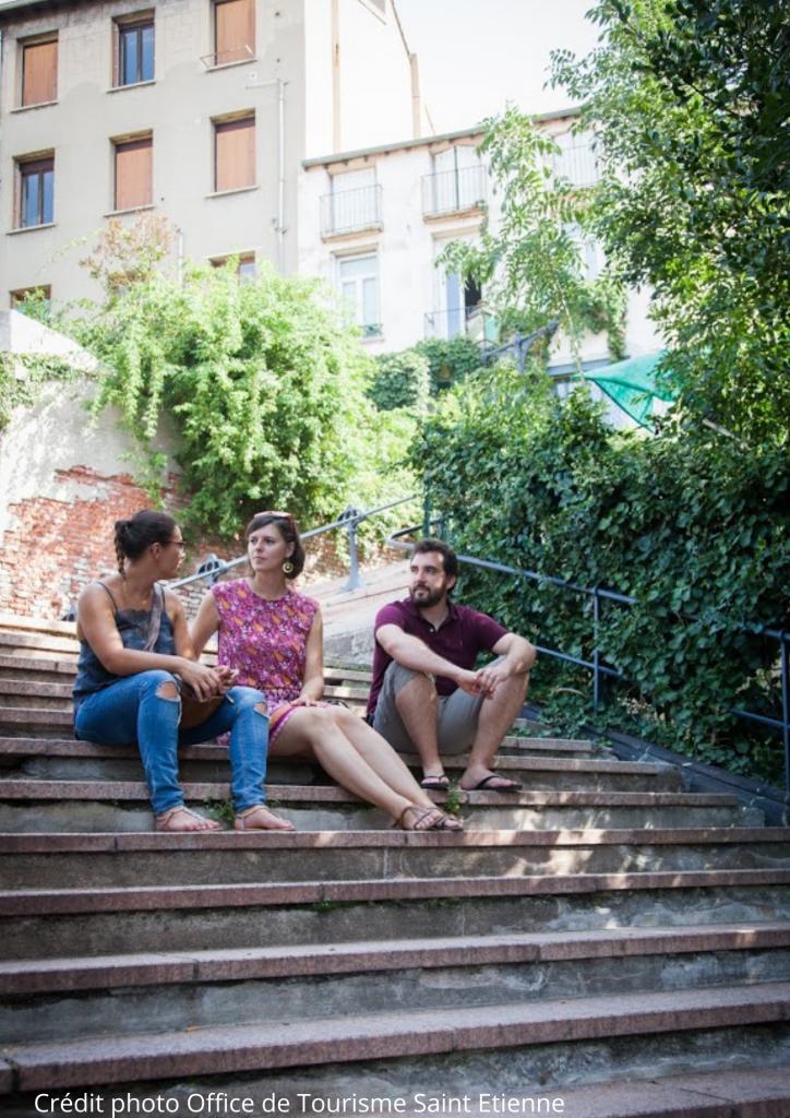 Deux touristes et un Greeter sont assis sur des marches à Saint-Etienne